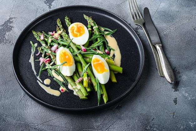 Asperges met eieren en franse dressing met dijon-mosterd, ui gehakt in rode azijn taragon op grijze gestructureerde achtergrond, zijaanzicht.