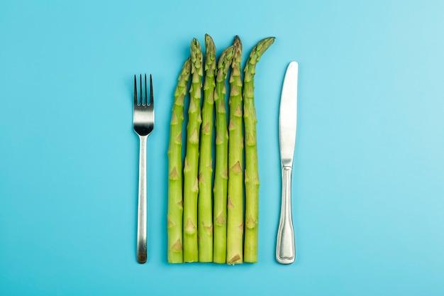 Asperges met vork en mes geïsoleerd op blauwe achtergrond