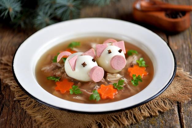 Aspic met vlees, varkensgelei is een feestelijk traditioneel russisch gerecht versierd met gekookte eieren in de vorm van schattige varkens.