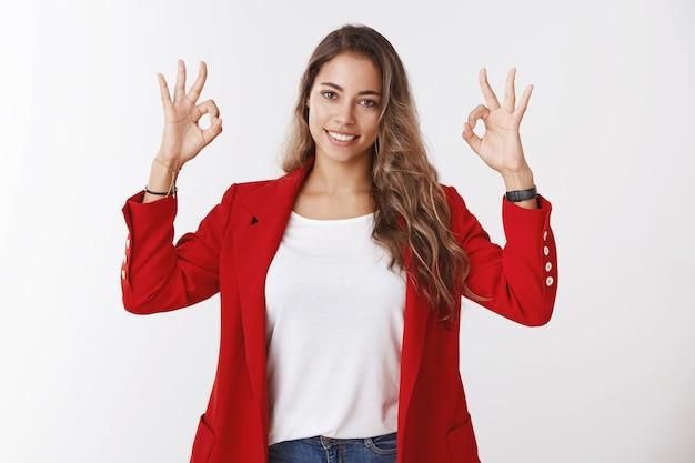 Assertieve, bekwame, zelfverzekerde jonge vrouw die zich gelukkig voelt helemaal zeker dat alles in orde is, oke ok gebaar laat zien glimlachend zelfverzekerd aangemoedigd promotie krijgen, gericht succes, leuk concept