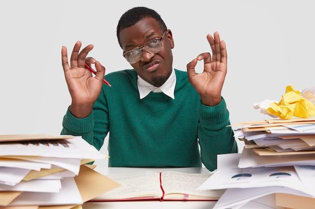 Assertieve jongeman met donkere huid draagt een bril, groene trui, maakt goed gebaar, keurt goed dat hij op tijd klaar zal zijn met werken