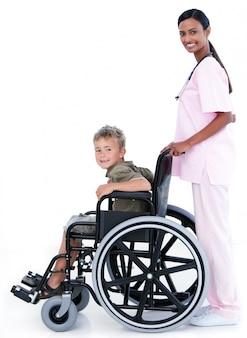 Assertieve vrouwelijke arts die een patiënt in een rolstoel vervoert