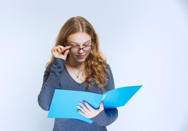 Assistent die de blauwe rapportmap opent en controleert.