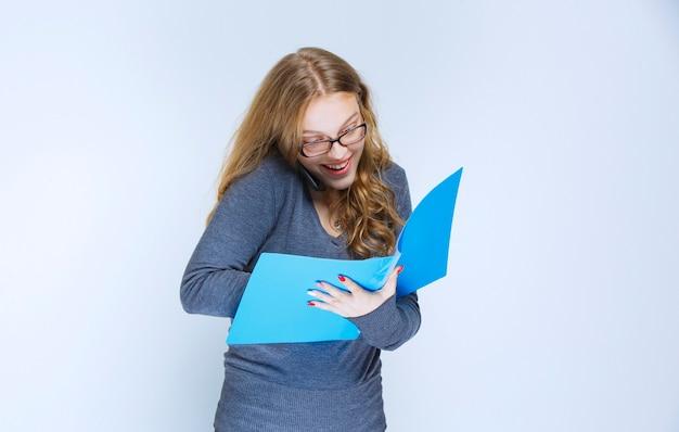 Assistent die tegen de telefoon praat en de blauwe map controleert en aantekeningen maakt, en ziet er erg gelukkig uit.