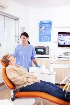 Assistent in tandheelkundige kliniek die oudere patiënt ondervraagt over tandproblemen. senior vrouw in gesprek met medisch verpleegkundige in stomatologie kantoor over tanden probleem.