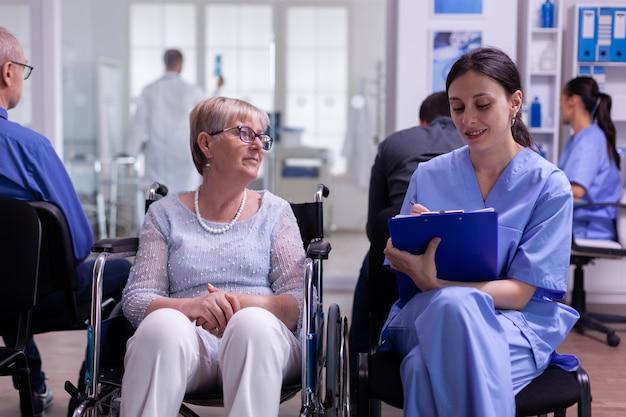 Assistent maakt aantekeningen op het klembord over gekke problemen van de patiënt, wachtend op een gespecialiseerde arts die op een rolstoel zit in de wachtkamer van de ziekenhuiskliniek
