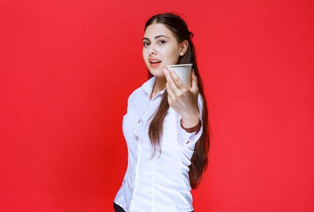 Assistent meisje biedt een kopje koffie.