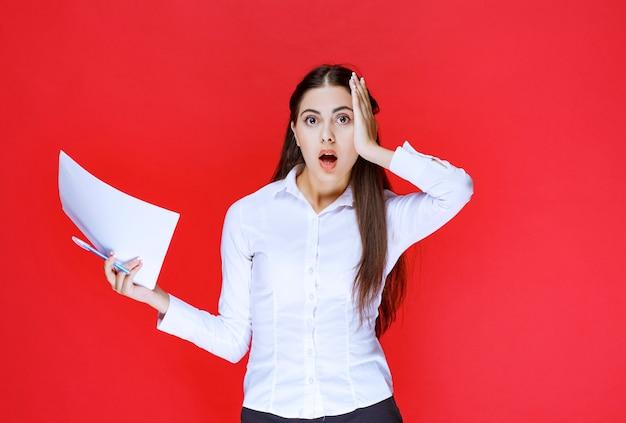 Assistent-meisje met papieren ziet er doodsbang uit als ze vergat taken af te ronden.