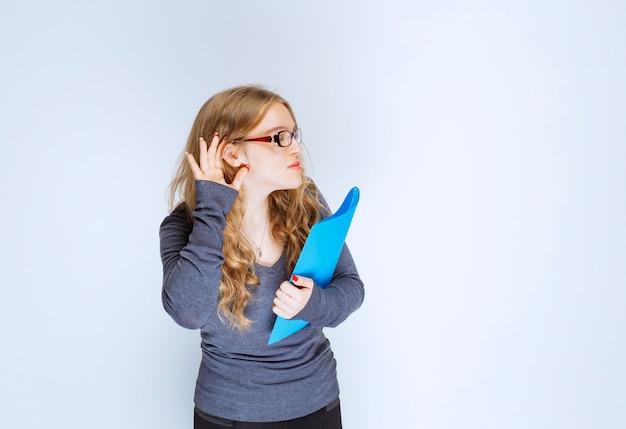 Assistent met een blauwe map die aandachtig luistert.