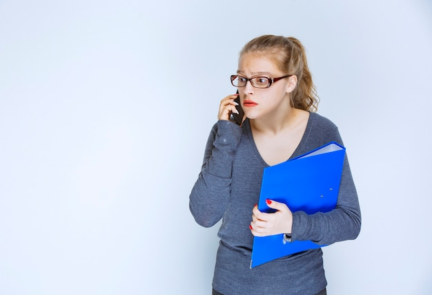 Assistent met een blauwe map die tegen de telefoon praat en ziet er gestrest uit omdat er iets mis is.