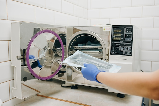 Assistent met steriele tandartshulpmiddelen. steriliseren van medische instrumenten in autoclaaf