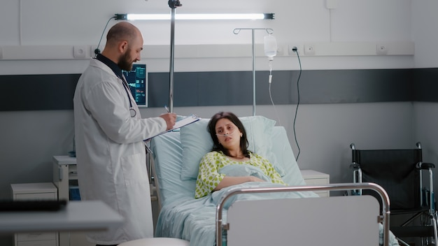 Assistent met zwarte huid regelen zieke vrouw bed tijdens ziekte herstel