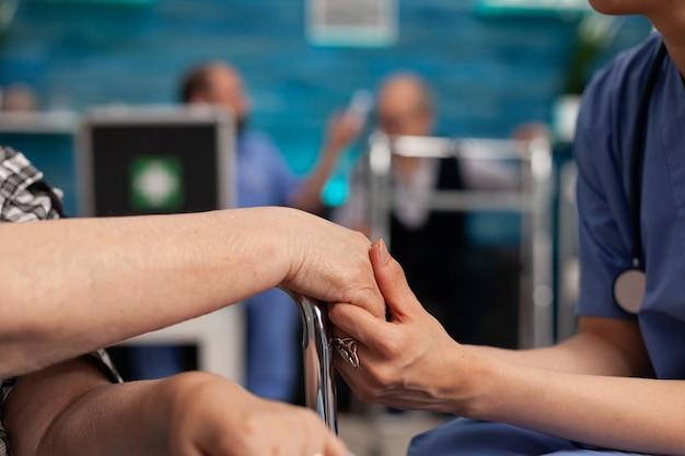 Assistent-ondersteuningsmedewerker die gehandicapte senior vrouwelijke patiëntenhanden vasthoudt
