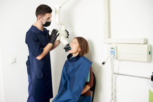Assistent-tandarts maakt een röntgenfoto van tanden naar een jonge vrouw in een modern medisch centrum