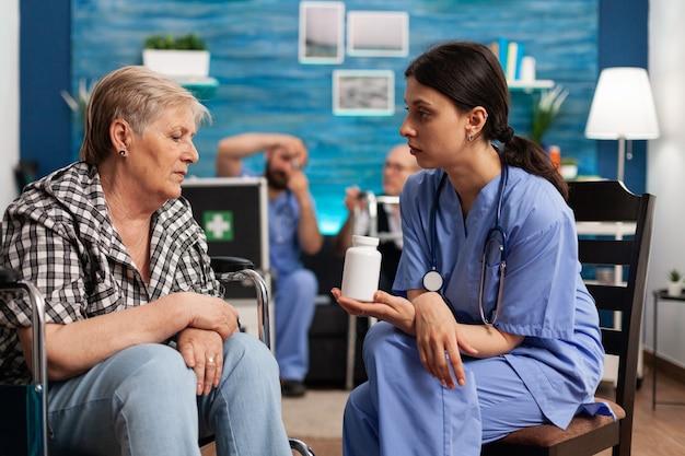 Assistent-vrouwenhelper die de behandeling van pillen uitlegt in gesprek met een senior oudere persoon