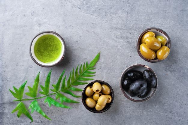 Assortiment antipasto, zwarte, groene olijven, pestosaus met basilicum in juskom op grijze achtergrond