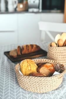 Assortiment brood, glutenvrij, mais en roggebrood in jute knutselmand op de keukentafel