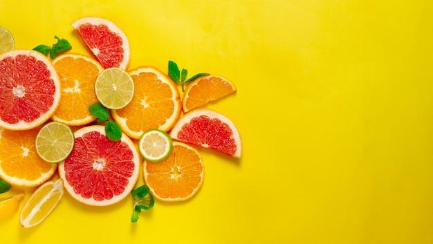 Assortiment citrusvruchten, op een gele achtergrond, bovenaanzicht, geen mensen, horizontaal,
