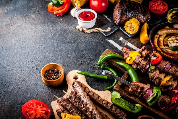 Assortiment diverse barbecue gerechten grill vlees, bbq party fest - shish kebab, worstjes, gegrilde vleesfilet, verse groenten, sauzen, kruiden, donkere roestige betonnen tafel, boven exemplaarruimte