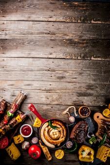 Assortiment diverse barbecue gerechten grill vlees, bbq party fest - shish kebab, worstjes, gegrilde vleesfilet, verse groenten, sauzen, kruiden, op oude houten rustieke tafel, boven exemplaarruimte