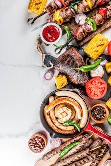 Assortiment diverse barbecue gerechten grill vlees, bbq party fest - shish kebab, worstjes, gegrilde vleesfilet, verse groenten, sauzen, kruiden, wit marmer oppervlak, boven kopie ruimte