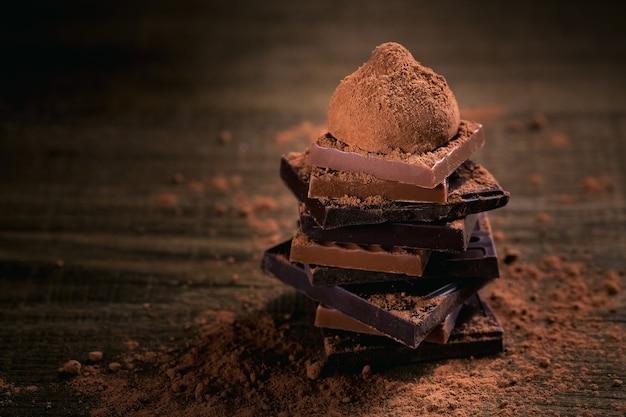 Assortiment donkere en melkchocolade, truffels. chocolade met cacaopoeder op donkere rustieke houten tafel. selectieve macrofocus. snoep en chocolade achtergrond.