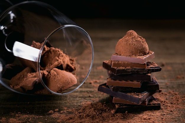 Assortiment donkere en melkchocolade, truffels. snoepjes in een glas. chocolade met cacaopoeder op donkere rustieke houten tafel. selectieve macrofocus. snoep en chocolade achtergrond.