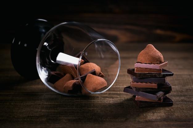 Assortiment donkere en melkchocolade, truffels. snoepjes in een glas op donkere rustieke houten tafel. selectieve macrofocus. snoep en chocolade achtergrond.