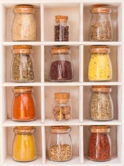 Assortiment droge kruiden in vintage glazen flessen in houten kist
