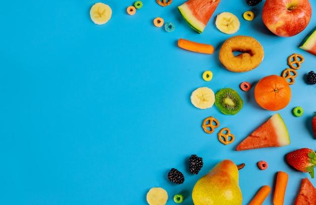 Assortiment groenten en fruit op blauwe oppervlakte gezond voedsel concept.