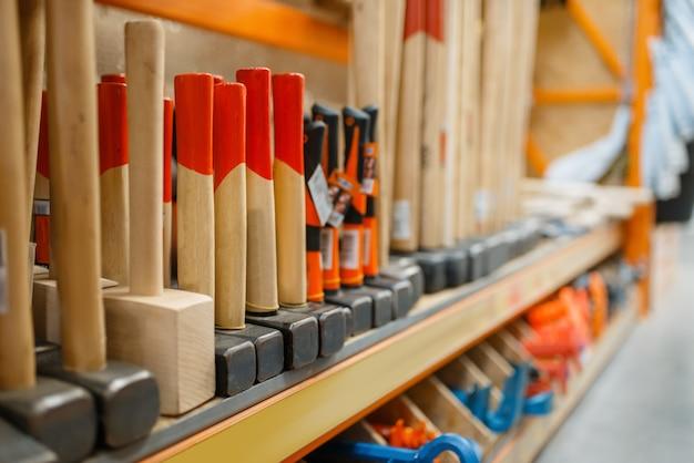 Assortiment ijzerhandel, plank met hamers, niemand. bouwmaterialen en gereedschappen keuze in doe-het-zelfzaak, rijen producten op rekken