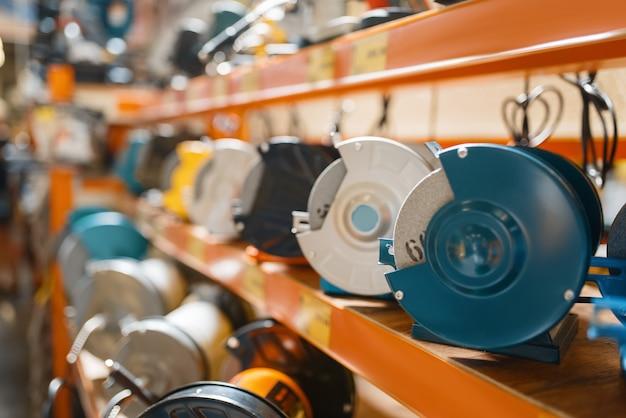 Assortiment ijzerhandel, plank met schuurmachines, niemand. keuze van elektrisch gereedschap in doe-het-zelfwinkel, rijen producten, elektrisch instrument