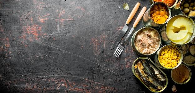 Assortiment ingeblikt voedsel in open aluminium blikjes. op donkere rustieke achtergrond