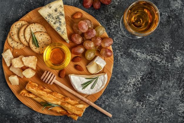 Assortiment kaas met wijn, honing, noten en druivenmost op een snijplank.