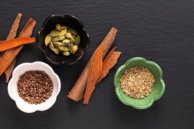 Assortiment levensmiddelenconcept oosterse kruiden kardemompeulen, korianderzaad, venkel en kaneel cassia bark sticks op zwarte leisteen