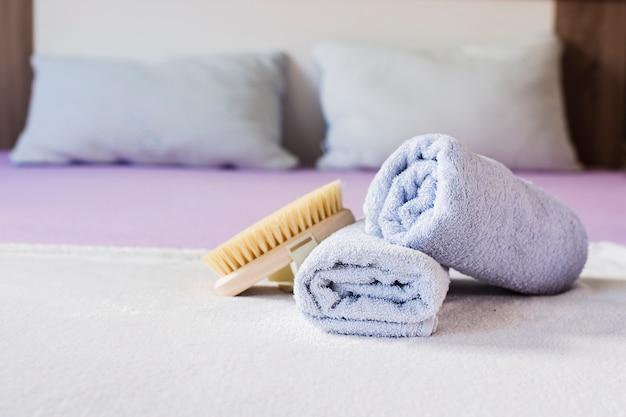 Assortiment met handdoeken en penseel op bed
