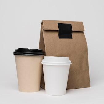 Assortiment met koffiekopjes en papieren zak