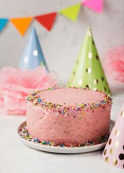 Assortiment met roze cake en feestmutsen