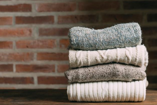 Assortiment met warme kleding en bakstenen muur