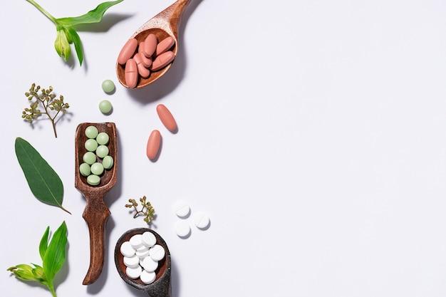 Assortiment natuurlijke kruidentabletten en pillen voor immuniteitsondersteuning in de houten lepels