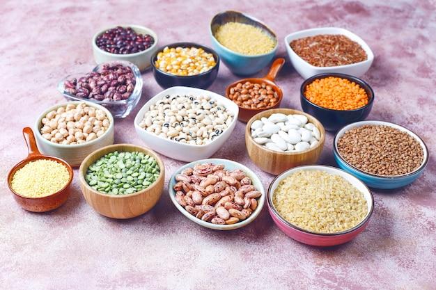 Assortiment peulvruchten en bonen in verschillende kommen op lichte stenen ondergrond. bovenaanzicht. gezond veganistisch eiwitrijk voedsel.