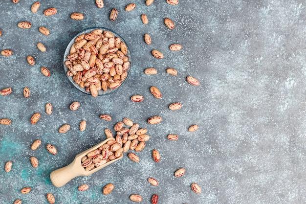 Assortiment peulvruchten en bonen in verschillende kommen op lichte stenen ondergrond. bovenaanzicht gezond veganistisch eiwitvoer.