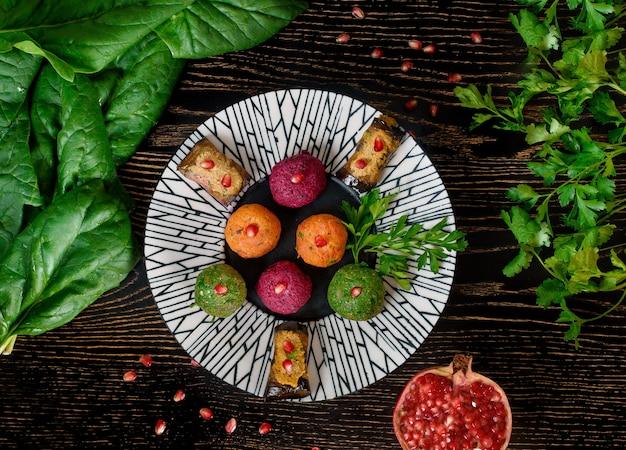 Assortiment pkhali van bieten, spinazie, wortelen, auberginebroodjes gegarneerd met peterselie en granaatappel. georgisch voorgerecht op een zwart-witte plaat met spinazie en peterselieblaadjes. bovenaanzicht.