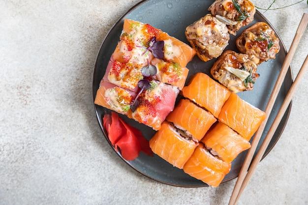 Assortiment sushibroodjes geserveerd met gemberstokjes op keramische plaat sushimenu japans eten