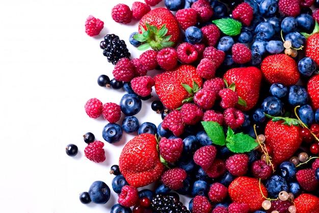 Assortiment van aardbei, bosbes, bes, muntblaadjes. voedselkader, grensontwerp. veganistisch en vegetarisch concept.