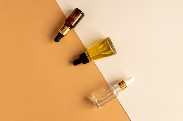 Assortiment van anti-aging collageen gezichtsserum in transparante glazen flessen op dubbele beige en grijze achtergrond.