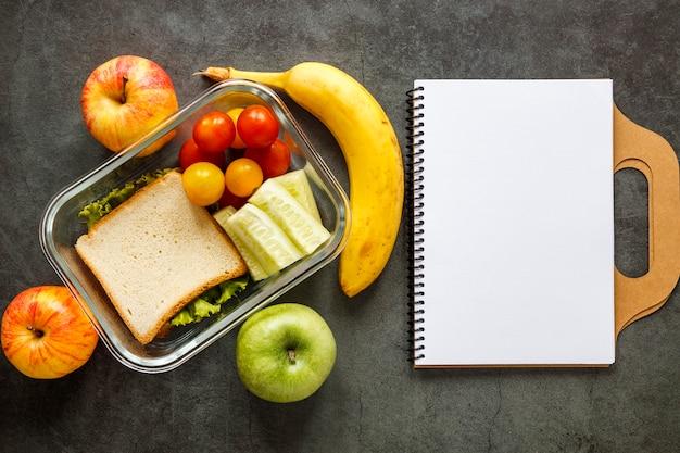Assortiment van batchvoedsel gekookt met een leeg notitieboekje