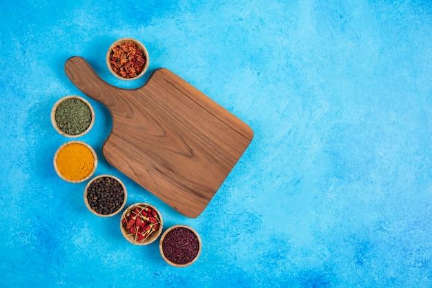 Assortiment van biologische kruiden rond houten bord.