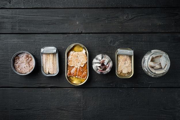 Assortiment van blikjes ingeblikt met verschillende soorten vis, op zwarte houten tafel