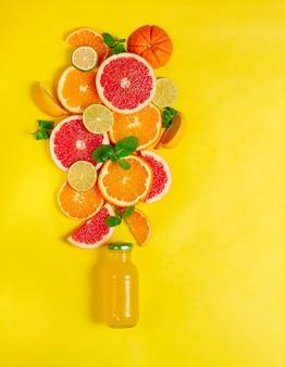 Assortiment van citrusvruchten, een fles sap, op een gele achtergrond, geen mensen, verticaal